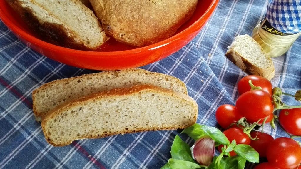 Pane semintegrale della cabotina intero e a fette con pomodorini, olio e aglio