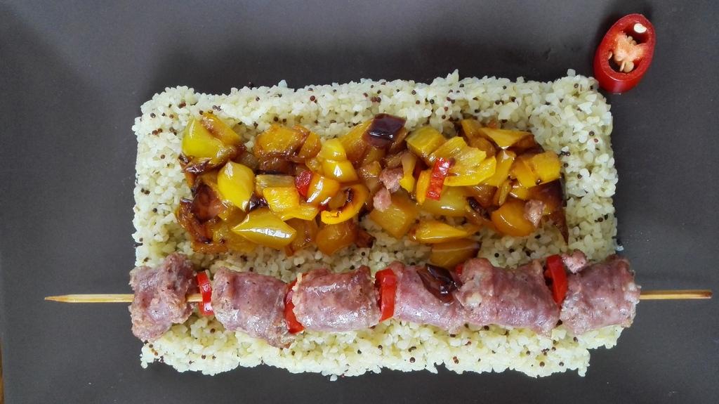 Piatto con un letto di bulgur e spiedini di salsiccia con peperoni