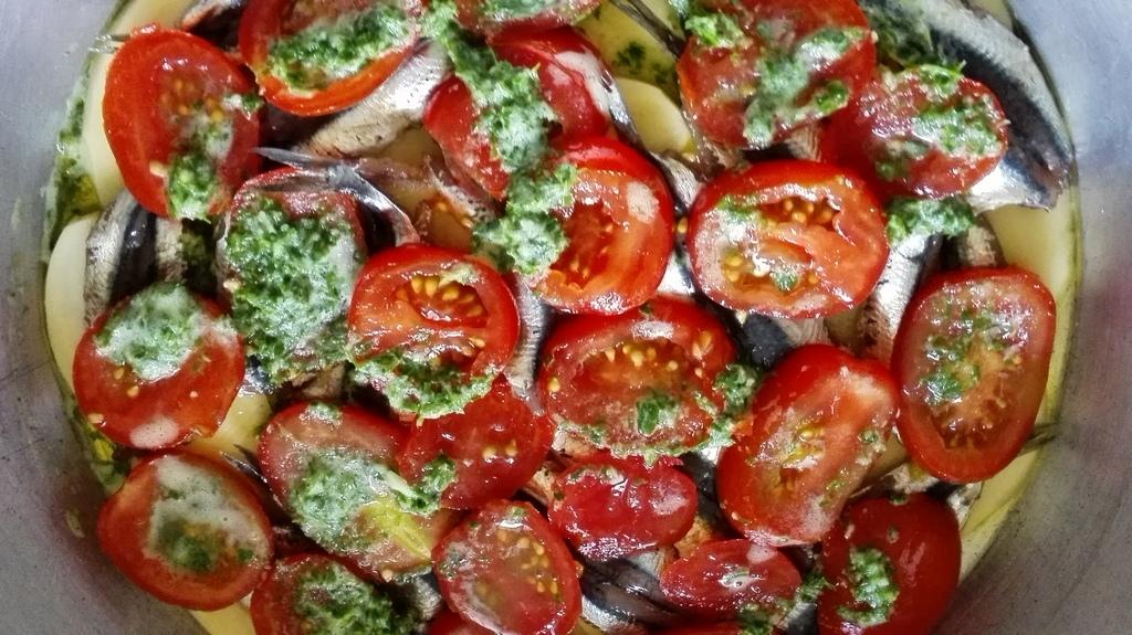 Strati nel tegame di patate, acciughe, pomodori e trito con vino bianco