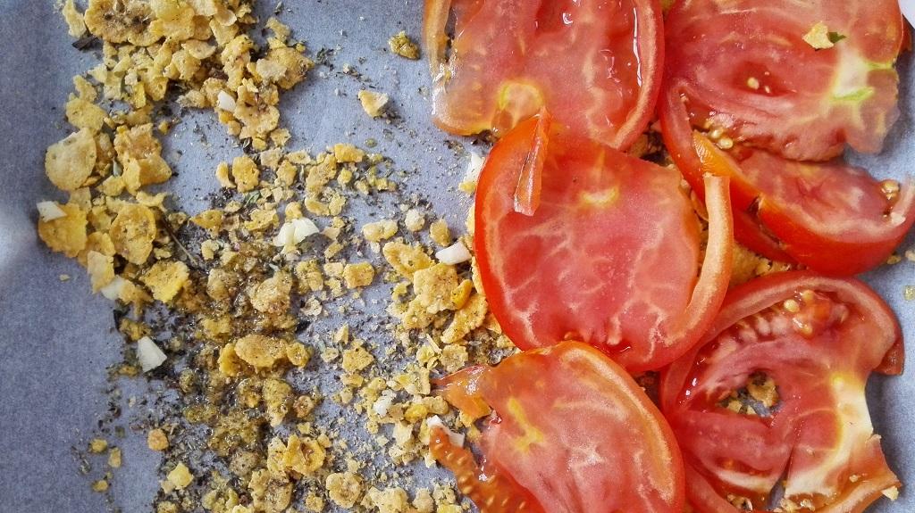 Sulla carta forno olio, cornflakes, erba luisa e aglio con sopra i pomodori