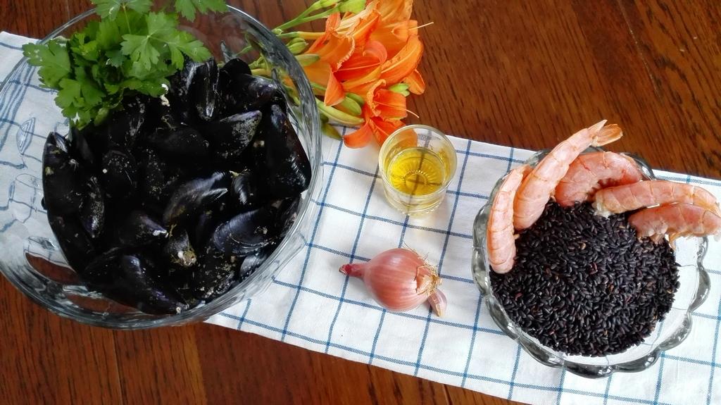 Ingredienti sul tavolo, muscoli, scalogno, aglio, riso venere e gamberi con decorazione di fiore