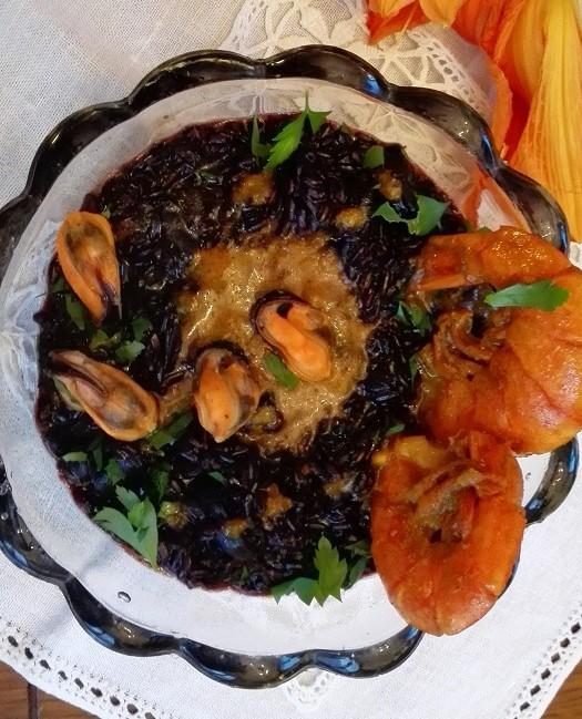 Ciotola trasparente con porzione di riso venere, sugo in centro e gamberi sul bordo