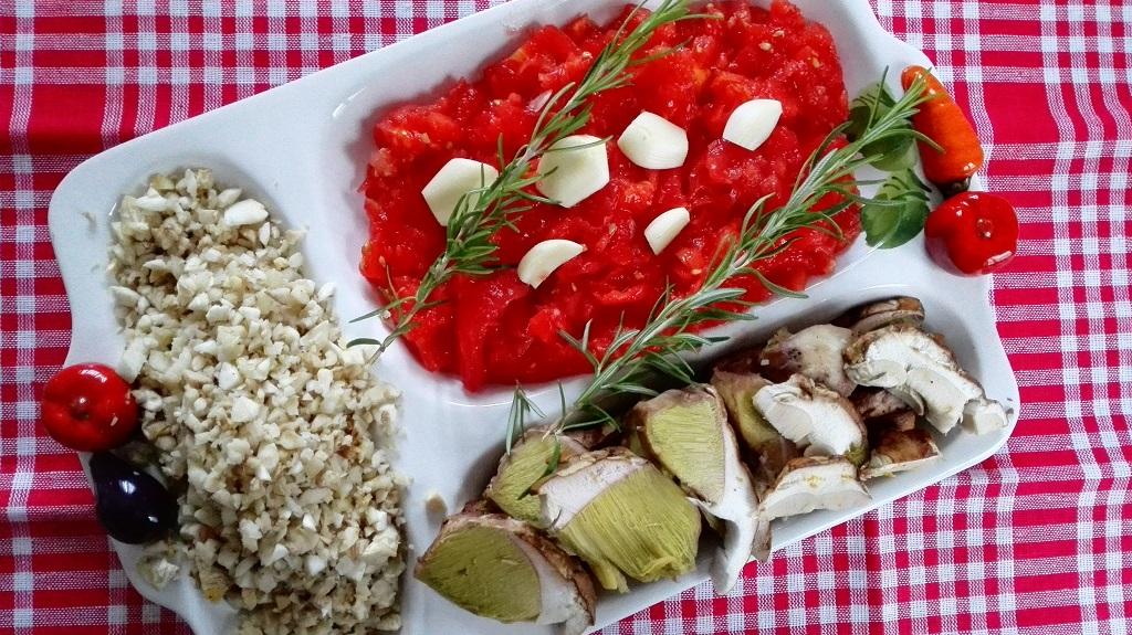 Ingredienti in vassoio con funghi tritati e a fette, pomodoro fresco sminuzzato, aglio e rosmarino