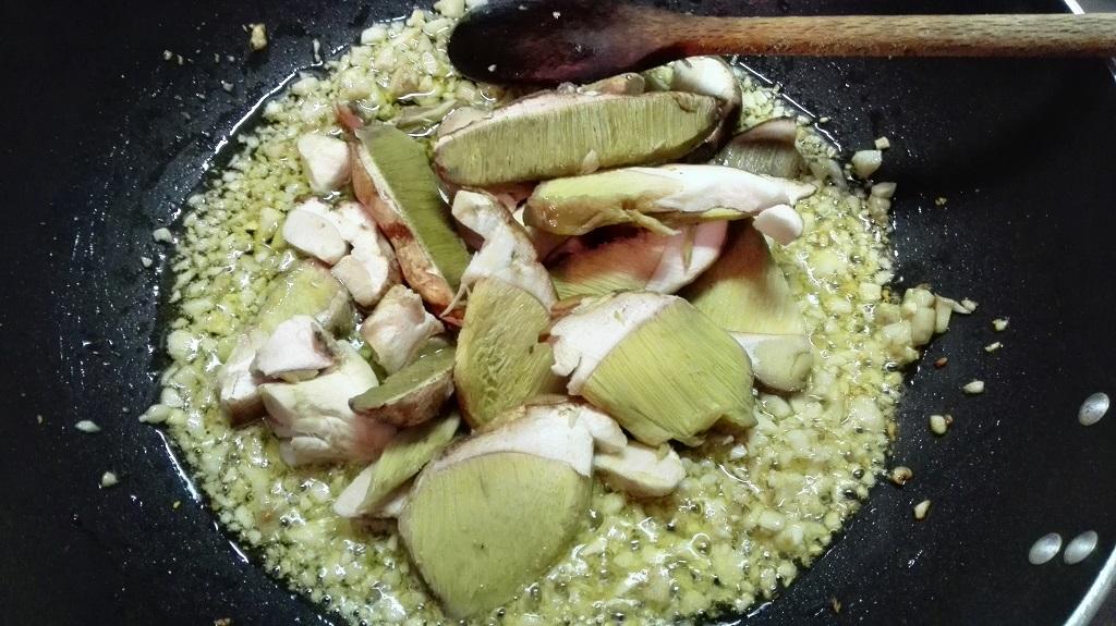 Soffritto con olio, spicchi di aglio, gambi tritati e cappelle a fette