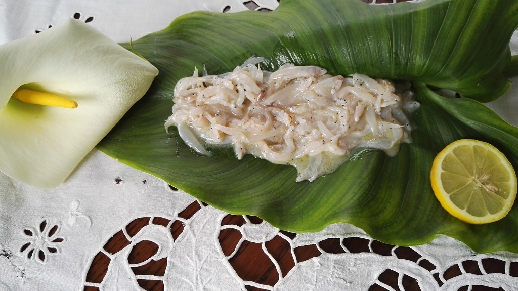 Bianchetti in marinata con olio, limone, sale e pepe su foglia di calla