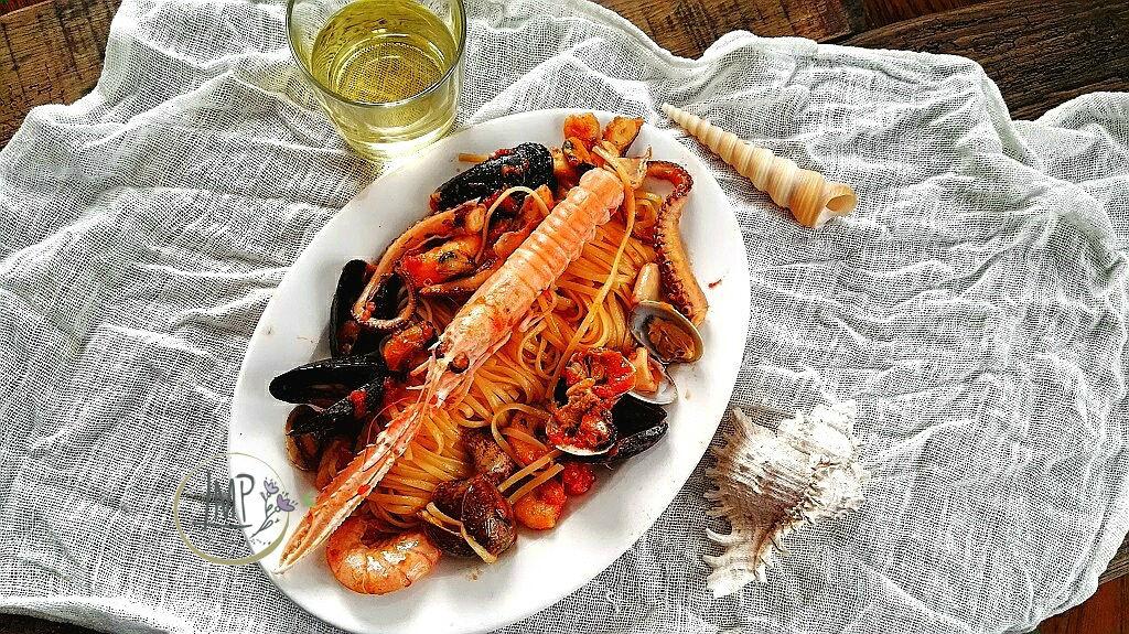 Pasta allo scoglio ligure nel piatto con vino bianco e conchiglie