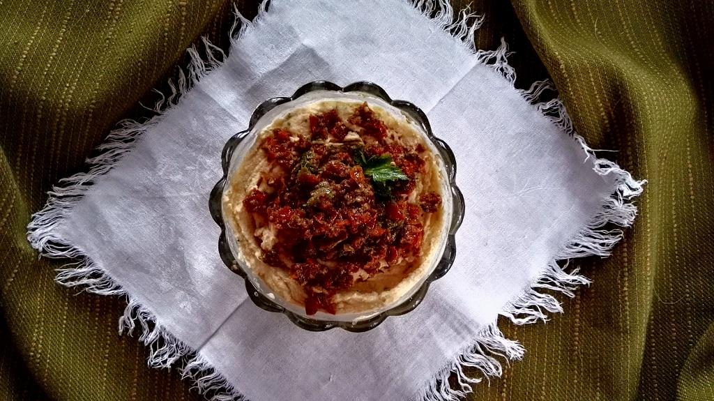 Hummus ai pomodori secchi in ciotola di vetro su tovagliolo bianco