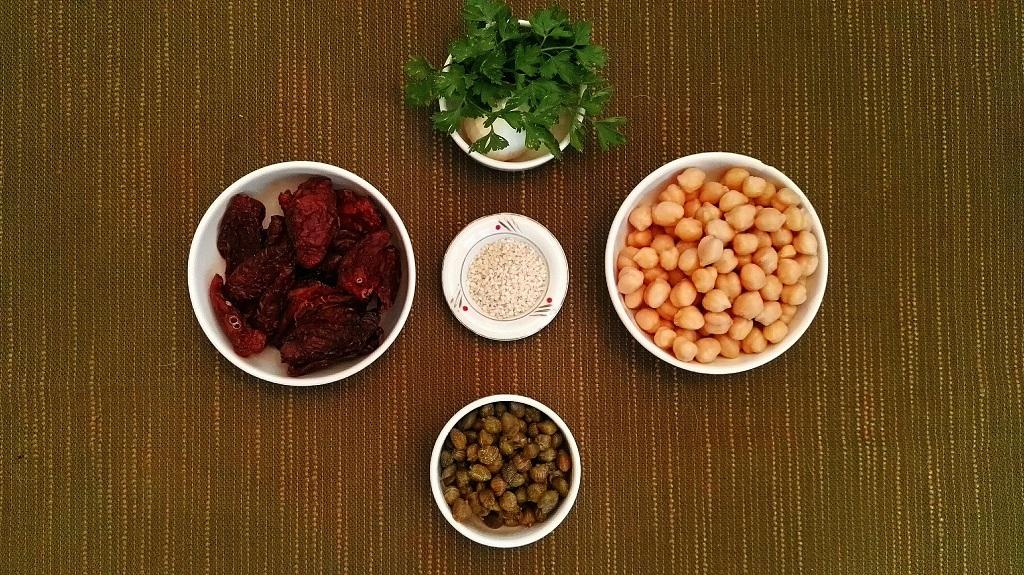 Ingredienti: ceci cotti, pomodori secchi, capperi, sesamo, aglio e prezzemolo