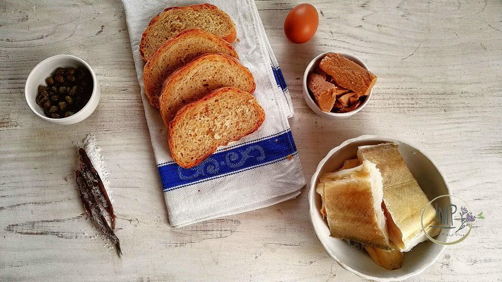 Bruschetta di insalata di stoccafisso ingredienti su tavola e salvietta