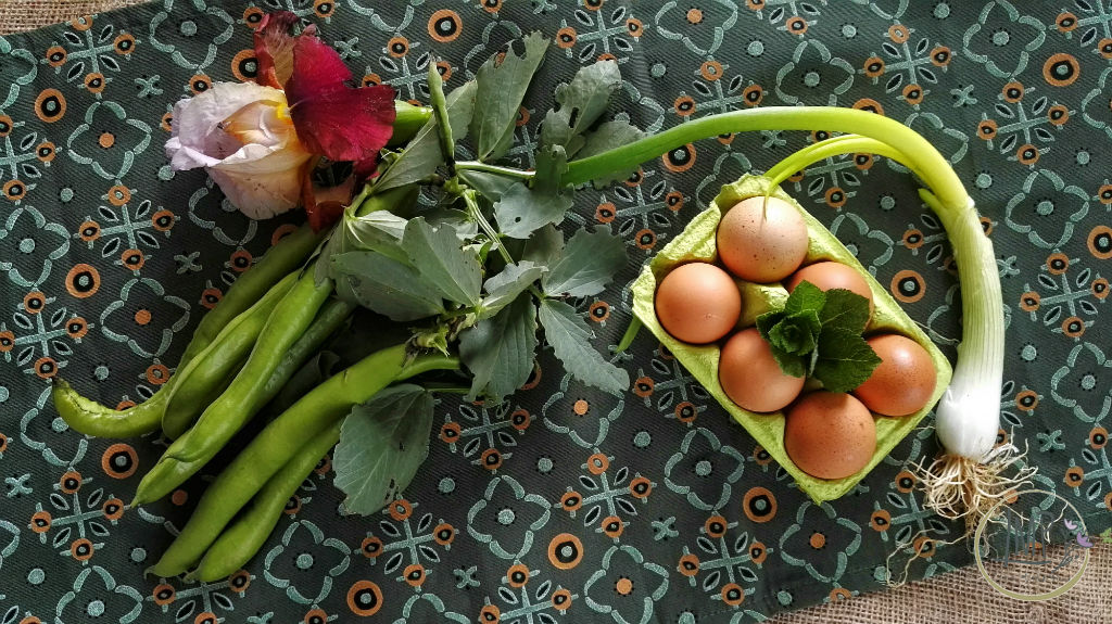Frittata di fave menta e cipolline Ingredienti su tovaglietta colorata