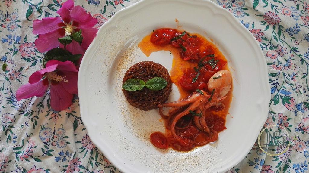 Riso rosso con moscardini nel piatto su tela fiorata